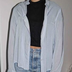 En tunn blå skjorta! Väldigt fint material och fin passform! Köparen står för frakten🥰