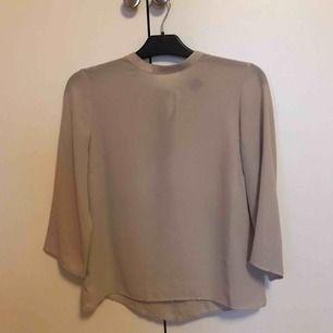 Säljer en beige blus från Gina tricot i strl 36. Trekvartsärm och med knytning i bak i ryggen. Tunn i materialet. Endast använd fåtal gånger så i mkt fint skick. Bra i storleken! Köparen står för frakten.