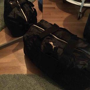Svart Puma väska med guldiga detaljer! Denna väska är i en perfekt storlek enligt mig eftersom att den är lite mindre än de vanliga träningsväskorna. Väldigt bra skick då den sällan kom till användning🥰köpt för 999kr  Pris kan diskuteras