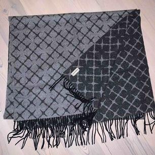 By Malene Birger halsduk i ull och kashmirblandning. Ljusgrå med mörkgrått mönster på ena sidan och tvärtom på andra. Supermysig halsduk i jättebra skick, använd ca 3 gånger. Nypris 1399kr.  Kvitto finns ej på grund av att jag fick den i present.