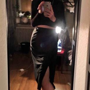 Lång kjol som går att knyta upp då den blir kortare. Snygg slits och spets-kant längst ner.