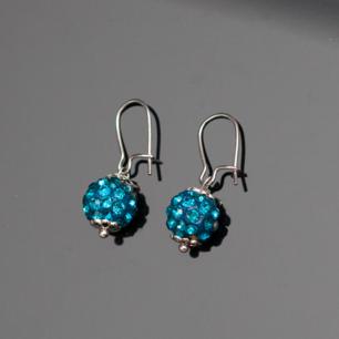 Fina silverfärgade örhängen med blå pärlor. Krokarna ska vara nickelfria enligt leverantör.