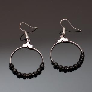 Fina silverfärgade örhängen med svarta pärlor i olika storlekar. Krokarna ska vara nickelfria enligt leverantör.