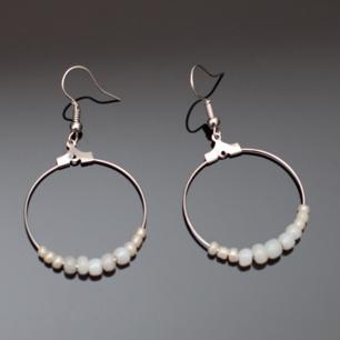 Fina silverfärgade örhängen med vita pärlor i olika storlekar. Krokarna ska vara nickelfria enligt leverantör.