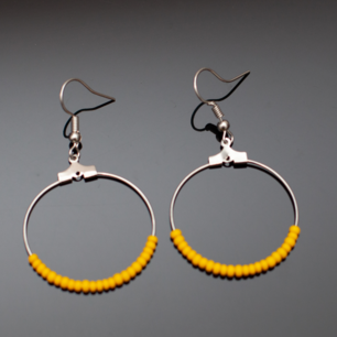Fina silverfärgade örhängen med gula pärlor. Krokarna ska vara nickelfria enligt leverantör.