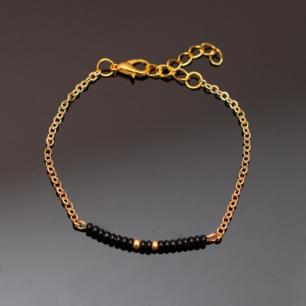 Handgjort armband i guld och svart. Kedjan är justerbar. OBS guldfärgen är inte lika gul/orange som på bilden