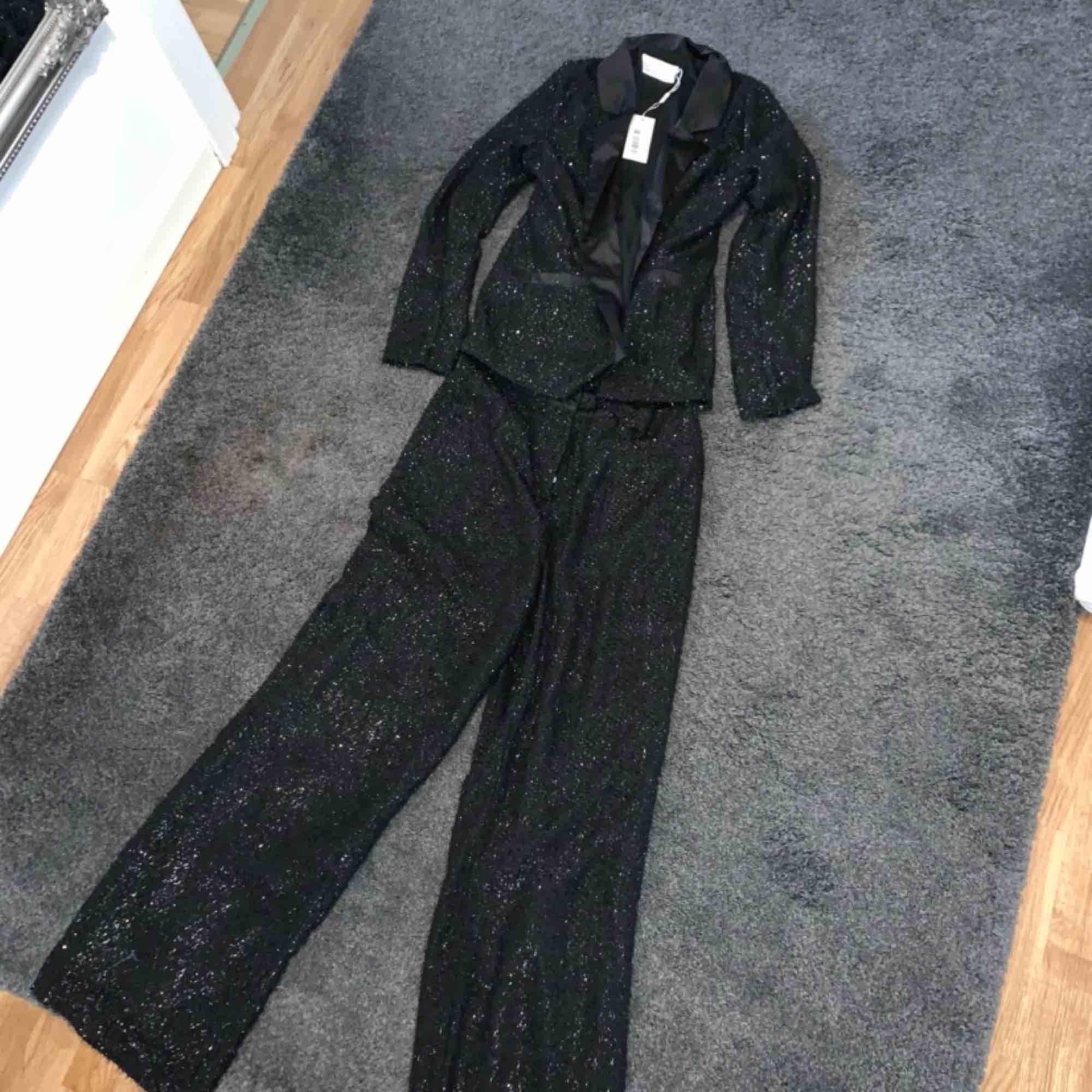 Glittrig kostym från Nelly, storlek 38 på kavajen och 40 på byxorna. Aldrig använd . Kostymer.