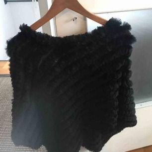 Helt oanvänd svart pälsponcho. Mycket fin över jacka, tjocktröja eller liva upp över en vanlig långarmad tröja
