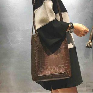 Superfin brun trendig väska med krododilläder mönster. Väldigt rymlig; storleken är 26x30x10 cm! Passar till alla outfits och perfekt till skolan! ⚡️⚡️⚡️