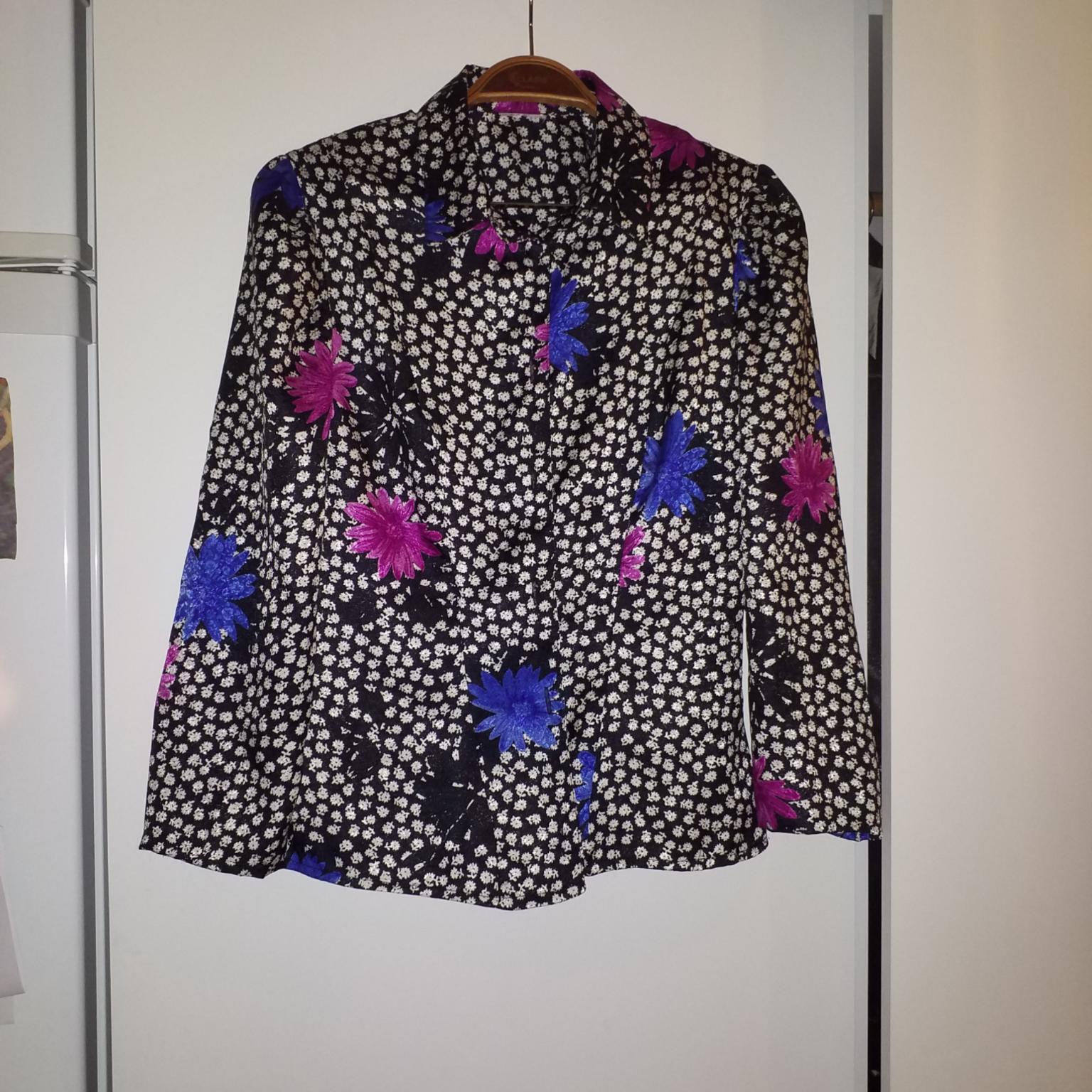 Tunn vintageskjorta i sidenlikt material med rosett i ryggslutet. Blusar.