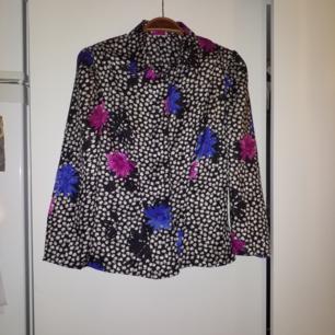 Tunn vintageskjorta i sidenlikt material med rosett i ryggslutet