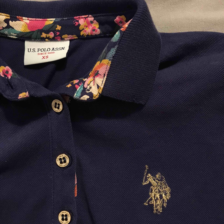 Marinblå pikétröja från Ralph Lauren med fina blomdetaljer på insidan kragen <3 tyvärr för liten för mig :( ordinarie pris: 600kr. Toppar.