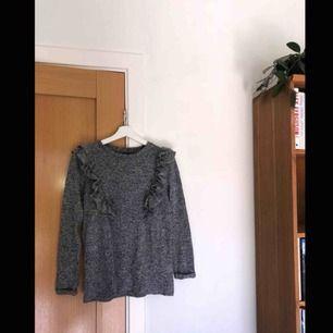 Grå långärmad tröja med volanger, storlek S.