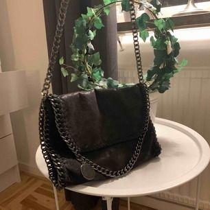 Fin svart, lite glittrig väska. Den har tre innerfack, ett med dragkedja och två utan. Dock är den magneten man stänger väskan med sönder, men finns en stor dragkedja Kan mötas i Sthlm & fraktar (frakt ingår i priset)