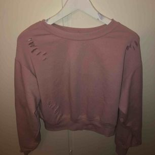 Rosa croppad sweatshirt från Bershka. Tröjan är oversized. Den har även tillgjorda hål lite överallt i tröjan vilket är en snygg detalj. Säljes pga att jag ej har användning för den.