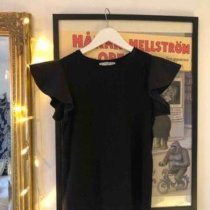 Superfin och basic t-shirt med volanger på ärmarna som inte kommer till användning längre. Som ny! Frakt tillkommer