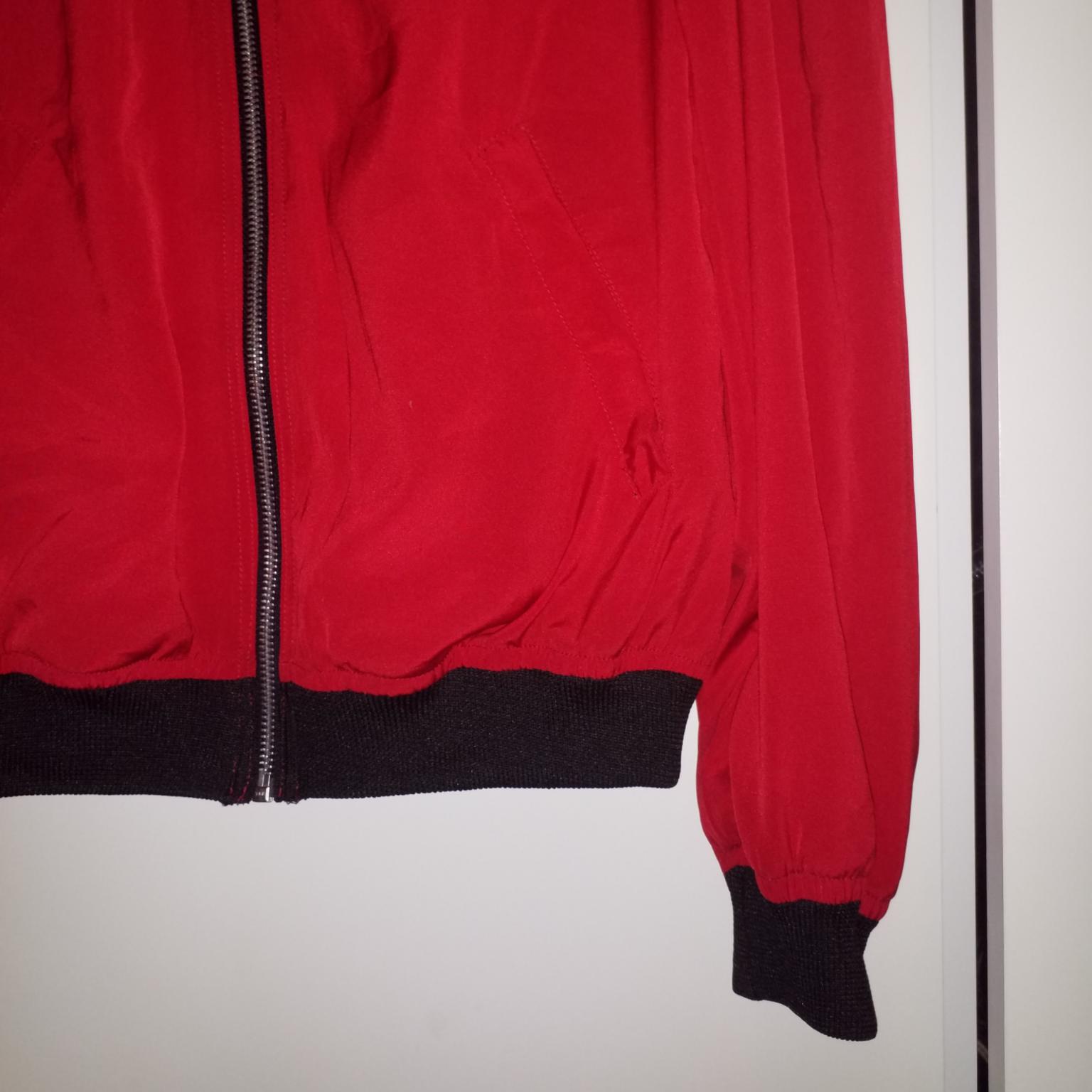 Tunn jacka/kofta i rött lite glansigt material med muddar, från Beyond Retro. Tröjor & Koftor.