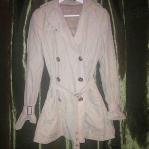 Supersnygg Beige kort trench coat med silvriga knappar och spännen i lätt använt skick, från tidigt 2000 tal!  Frakt ingår ej :/