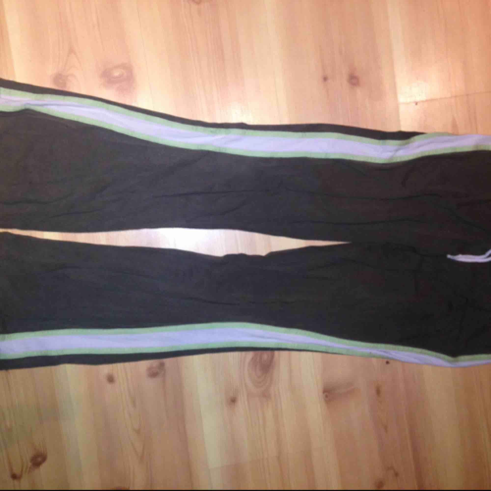 Militärgröna utsvängda mjukisbyxor i 2000tals anda! Vitgrå och ljusgröna ränder längs sidan. Från Sydafrika!. Jeans & Byxor.