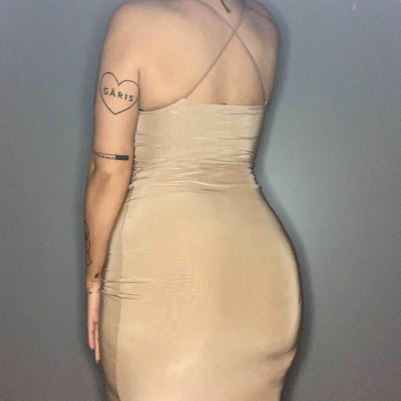 Beige bodycon klänning i slinky material, når till knäna på mig som är 170. Mycket bra skick.. Klänningar.