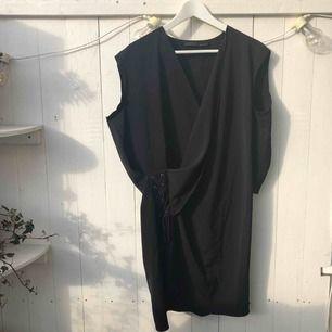 Svart klänning från Allsaints med snygg snörning i midjan. Storlek 40, längd 90cm Endast använd ett fåtal gånger