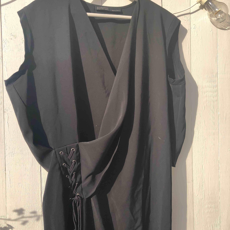 Svart klänning från Allsaints med snygg snörning i midjan. Storlek 40, längd 90cm Endast använd ett fåtal gånger. Klänningar.