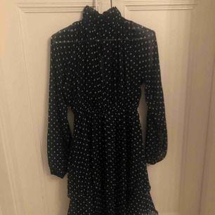 """Mörkblå klänning med vita prickar med hög krage. Väldigt """"flowy"""" och somrig. Frakt ingår"""