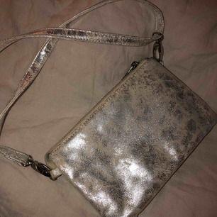 Super fin väska i silver. Mycket rymlig trots liten. Har tre fack. Går att justera banden och även ta bort dem och använda den som clutch🌼🌸🌟🌺💫