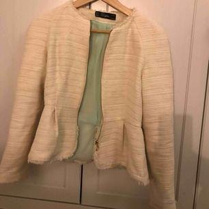 Superfin Zara jacka i en créme vit färg med en fin turkos färg inuti. Jackan har lite glitter i som syns i vissa ljus. Skulle även passa en person som vanligtvis har XS