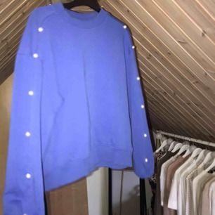 Sweatshirt i klarblå färg med pärlor på sidorna