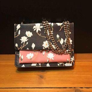 En blommig handväska ifrån mango med en jättefin rosa färg i mitten. Väskan har 3 olika fack. Köpt för 3 år sedan men i superfint skick.  Kan frakta om köparen står för kostnaden. Skriv om du undrar något! :)