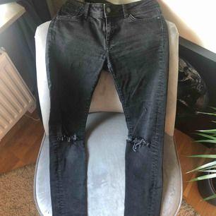 Svarta jeans med egen klippta hål vid knäna.
