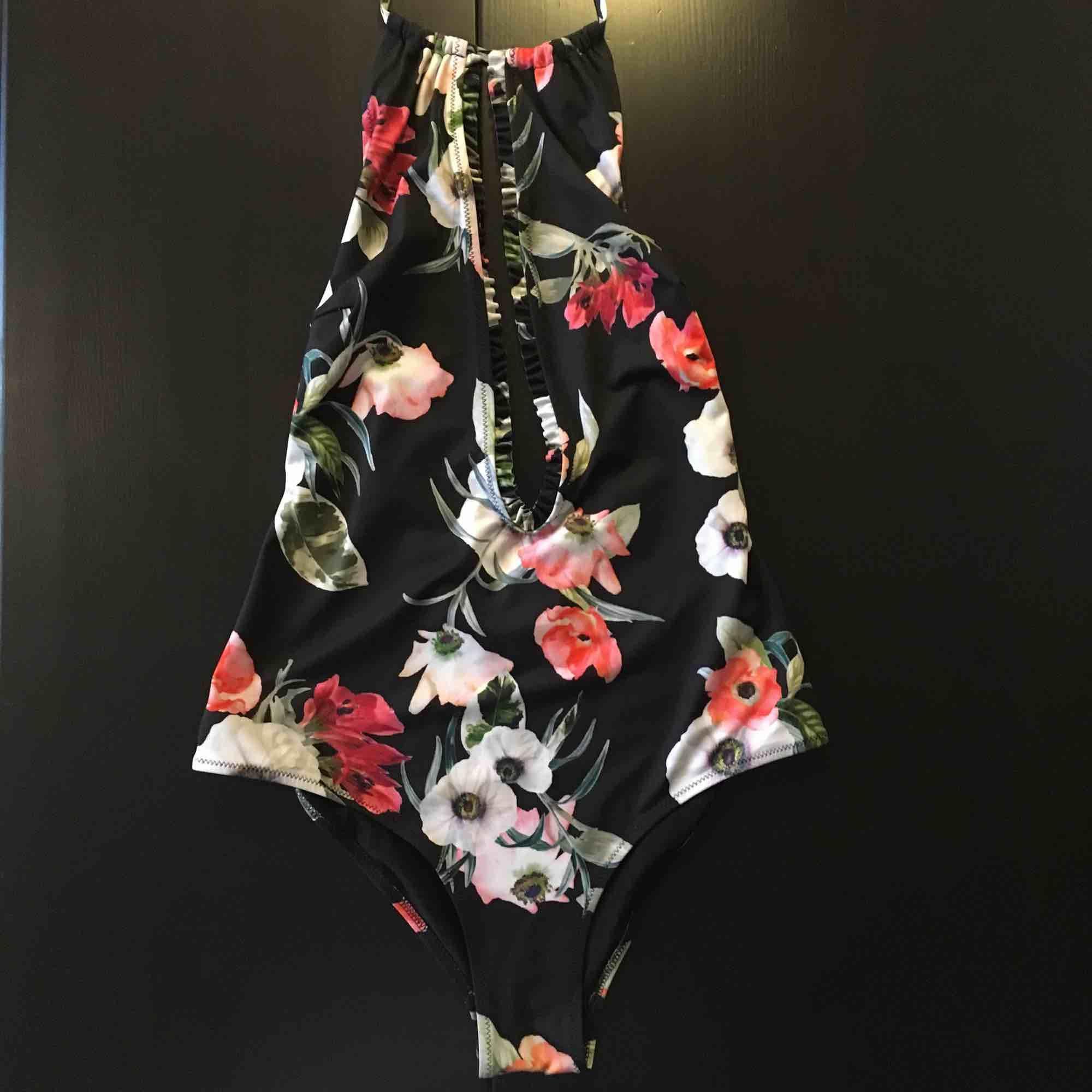 Halterneck-baddräkt från HM. Svart botten, blommigt mönster. Lite volanger/ruffles. Låg rygg. Supersexig! . Övrigt.