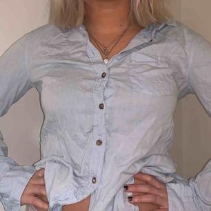 Himmelsblå skjorta från H&M med brun-melerade knappar och en randig lapp på ena armbågen. Kollektion- L.O.G.G. (Labour of Graded Goods)