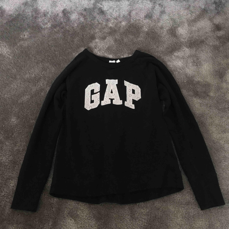 Sweatshirt från gap. Svart med vit text som är i ett blommigt broderi liknande tyg. Använd men i bra skick. Köpt i london. Storlek xs men stor i storleken. . Huvtröjor & Träningströjor.