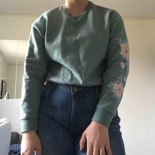 Grön croppad sweatshirt från forever 21 med broderade blommor på ärmarna. Nästan aldrig använd. Jättefint skick. Storlek s och normal i storleken.