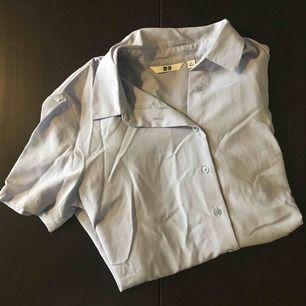 Kortärmad skjorta från Uniqlo. Lite skrynklig på bilden... mycket gott skick! Lavendellila färg.