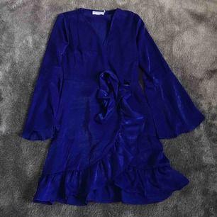 Jättefin mörkblå klänning i siden imitation. Aldrig använd. Från nakd. Kimono liknande som man kan knyta fram eller bak. Bredare längst ner på armen och volang längst ner på klänningen.
