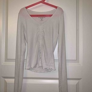 Vit tröja med detaljer i skönt material. Storlek xs, knappt använd! Köpt från Hollister i London. 70kr plus frakt, kan mötas upp i Sthlm