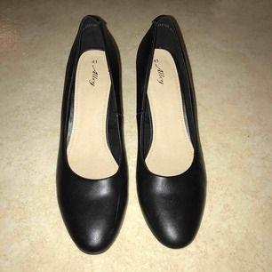 Oanvända, svarta klackar i skinnimitation från märket Alley från din sko. 7,5 cm bred klack. Endast testade, prislappen kvar (299kr). Köparen står för frakt.
