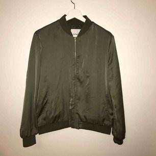 Militärgrön, tunn bomberjacka från STAY köpt på Carlings. Använd 5 gånger, fläcken på ryggen syns mer på bild än i verklighet, samma med fickan (som går att laga). Passar M och möjligtvis XL. Köparen står för frakt.