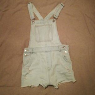 Ljusblåa hängselbyxor (shorts) som är storlek S/M. Passar bra till mycket.