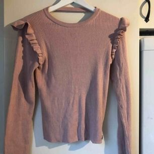 En långärmad rosa tröja, volanger på axlarna, lite öppet i nacken! Skickas ej