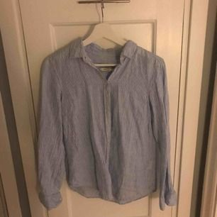 Vit och blå skjorta i 100% linne från Gina Tricot. Jättefint skick!   Frakt tillkommer.