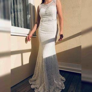 En vacker vit, glittrig spets klänning med jätte fina glittriga detaljer. Den verkligen glittrar i solen. Ger form till kroppen och är bekväm. Använd endast en gång. Passar såväl som balklänning, festklänning som bröllopsklänning.   Passa på