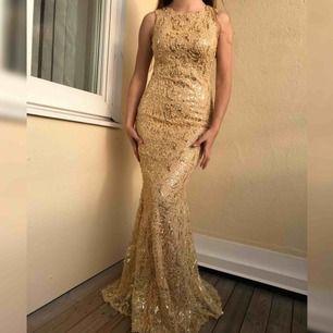En vacker guldig klänning med glittriga paljetter. Klänningen  är bekväm samtidigt som den formar kroppen och passar såväl till bröllop, bal som fest.    Passa på!