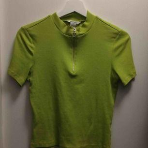 Skitsnygg lime/neongrön t-shirt med dragkedja köpt på Monki, sparsamt använd. Möts upp eller fraktar men köparen står då för frakt.