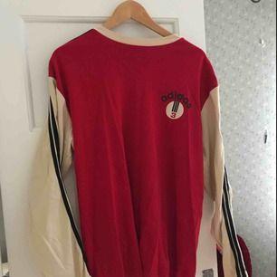 Snygg oversized Adidas tröja. Köpt på vintagebutik i Madrid, aldrig använd av mig. Fint skick, två nästintill osynliga rosa fläckar på ena ärmen (se bild 3) Storlek XXL, men skulle Medium. Jag har small och på mig är den lagomt oversized. Frakt tillkommer