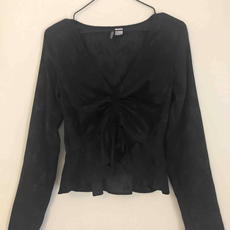 Snygg tröja som man kan dra ihop och knyta framtill. Den är svart med små skimrande rosor. Använd max 2 gånger så i toppen skick, frakt tillkommer. Toppar.