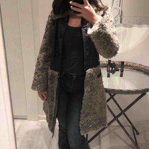 En grå kappa med hår får liknande detaljer runt jackan. Jackan är använd men är i bra skick.  Säljs pga ingen användning.